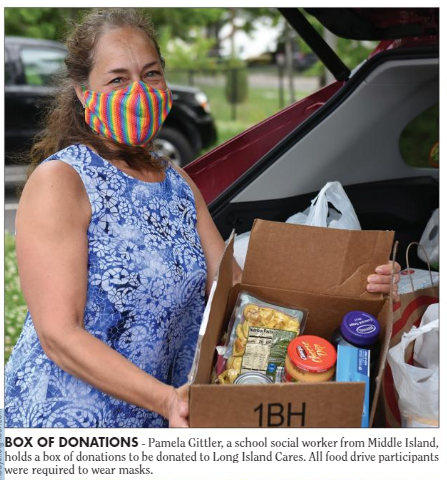 A picture of a woman in a blue floral shirt with rainbow mask holding a box of food