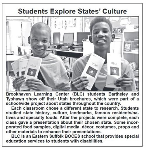 two students holding brochures and smiling at the camera
