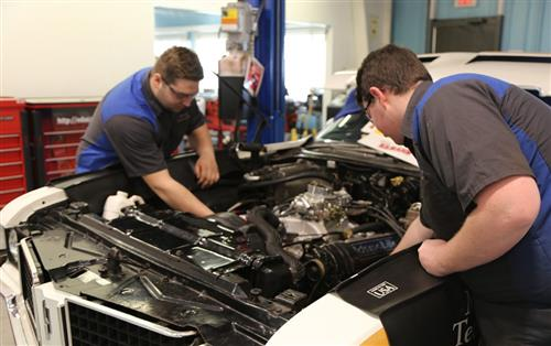 nick and adam working under the hood of a car