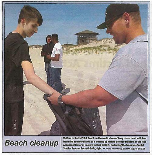An image of a scanned newspaper story showing a student putting trash in a garbage bag held by a man