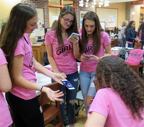 "Four girls look in their phones, all wearing pink shirts that say ""Think like a girl"" on them"