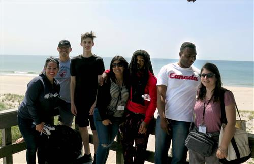 A group of students take a picture on a balcony with the ocean in the background