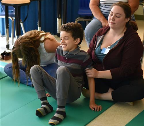 A boy gets into a yoga position with the help of an aid.