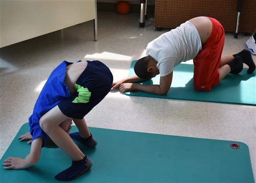 Two boys practice a forward fold in yoga, which involves bending at the waist