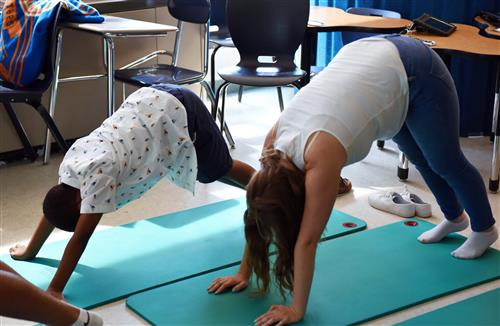A student and teaching assistant get into downward dog during Yoga Class