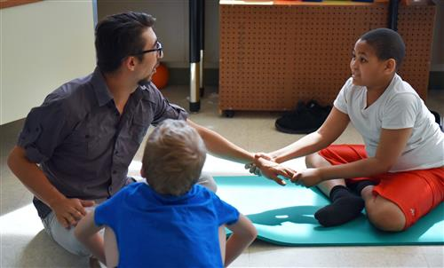 A teacher works with two students who are seated on yoga mats