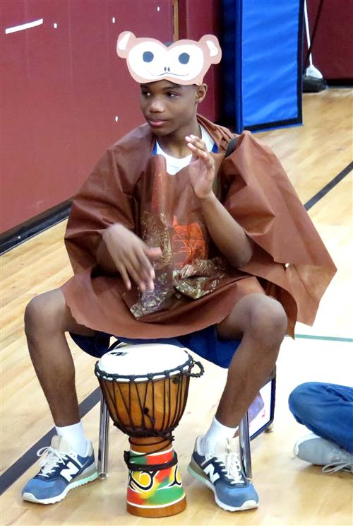 A student dressed as a monkey beats a drum