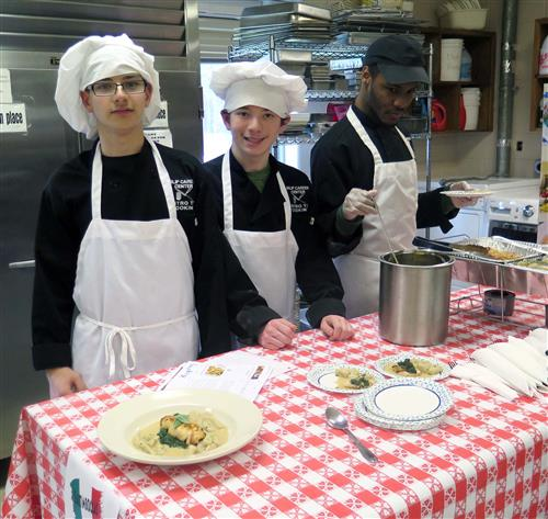 Three students wearing white chef's hats and aprons stand behind a table with a red and white gingham table cloth.