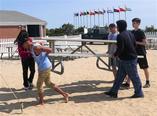 Five men work to lift a picnic table, carrying it over sand into a shady area