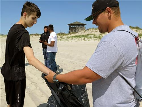 A student in a black shirt puts garbage in a garbage bag held by a man in a grey shirt