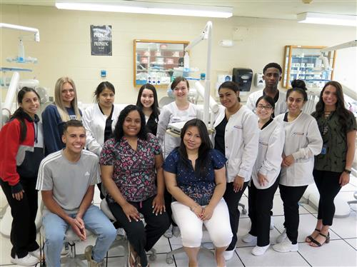 A group of 13 people stand in front of dental equipment and smile.