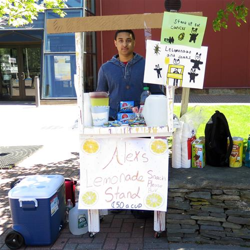 "A student stands behind a lemonade stand titled ""Alex's Lemonade Stand"""