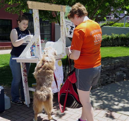 A girl serves lemonade to a woman wearing an orange shirt with a dog.