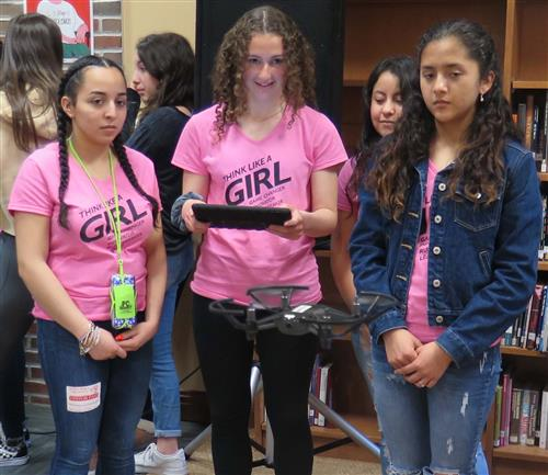 Three girls in pink shirts smile as they look at a drone flying in front of them - being controlled by an iPad