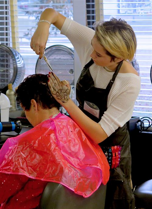 student cuts customer's hair