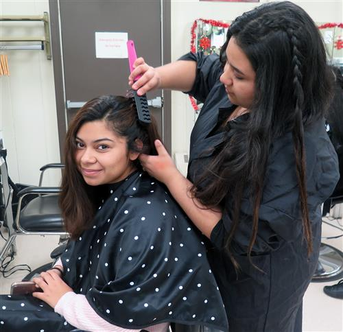 student brushes the hair of a customer