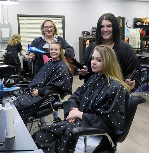 students standing behind styling chairs smiling