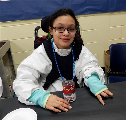 Student in wheelchair holding can of soup