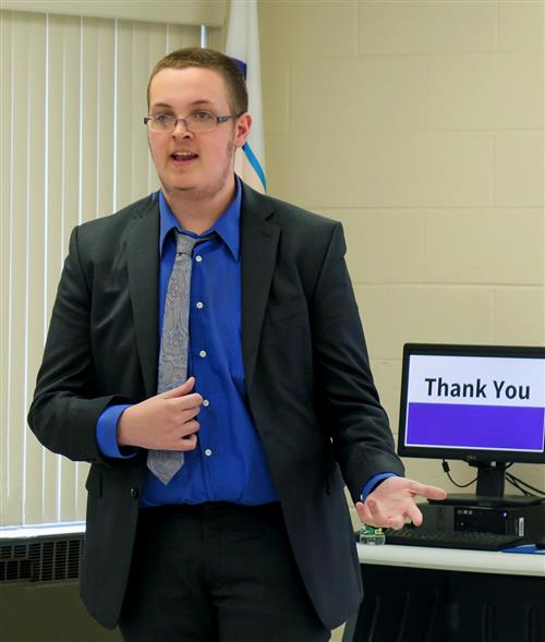 "A student wearing a blue shirt and gray tie gives a presentation with a computer with the words ""thank you"" in the background"