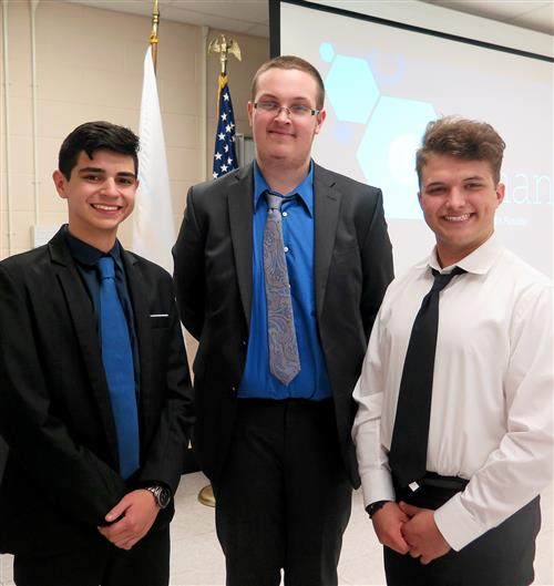 Three students in suit and ties stand beside one another smiling