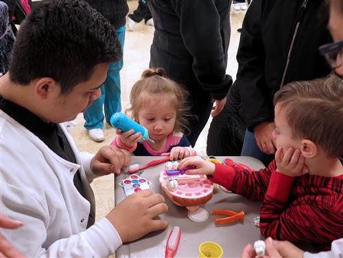 Two preschoolers and a dental student play with a toy dental set