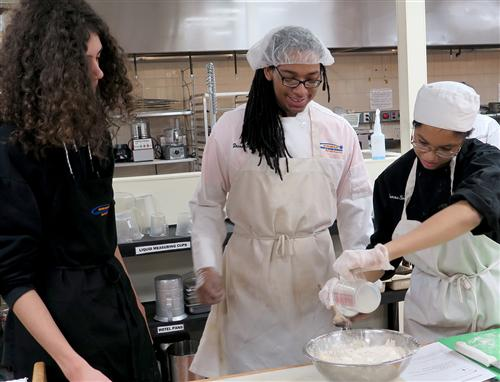 Food Prep students mix dough for bread while STEM High School History student watches