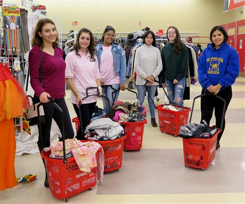 Group shot of students in Savers with baskets of clothes
