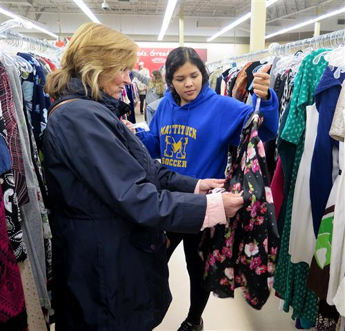Student and teacher looking through racks of clothes in Savers
