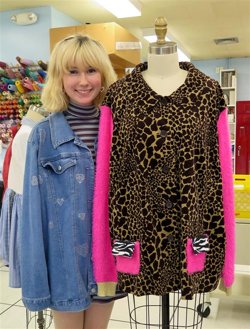 Student next to a jacket with contrasting animal prints