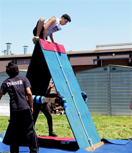 Student scaling a wall in the obstacle course