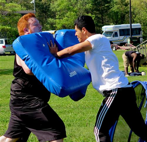 One student pushing against another who is holding large pads
