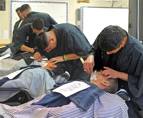 A row of barbering students performing the straight-edge shave on fellow students