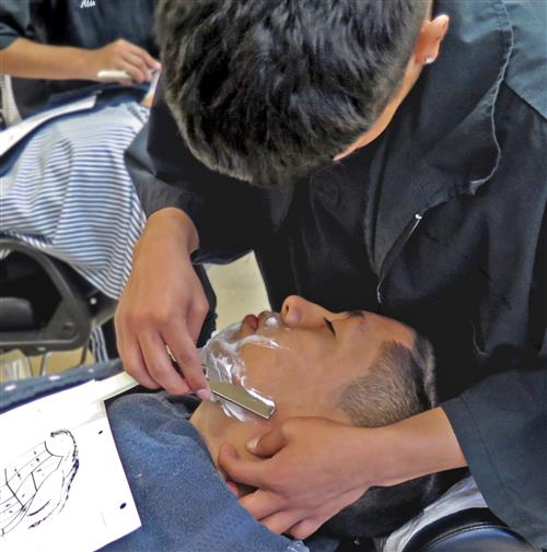 Close-up image of a student receiving a straight-edge shave