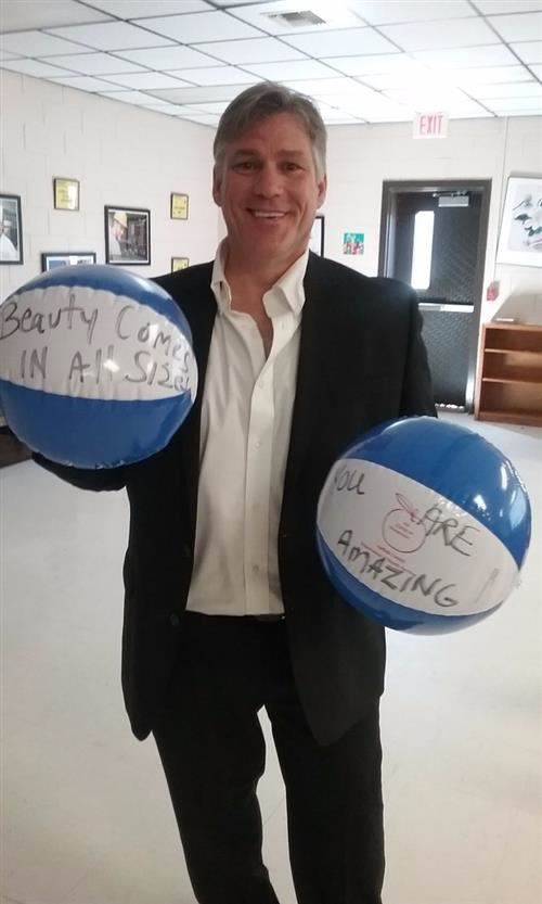 John Martin holding beach balls with inspiring words on them.