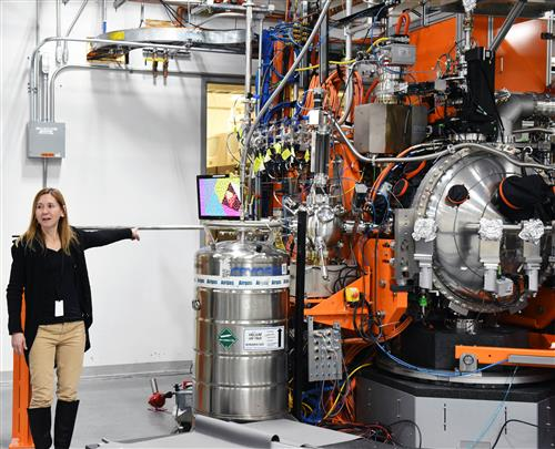 A woman stands in front of a piece of scientific equipment