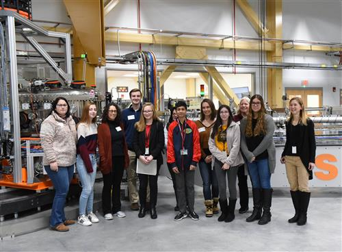 Students stand in front of a piece of machinery at BNL