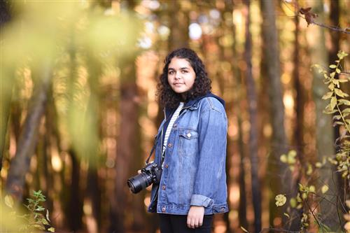 Student in woods with camera