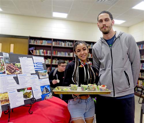 student holding a tray of food samples, standing next to teacher