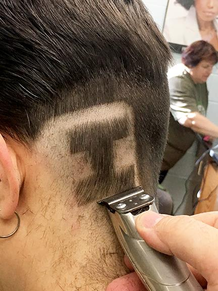 """Close-up of an """"I"""" being etched into the scalp of a teacher"""