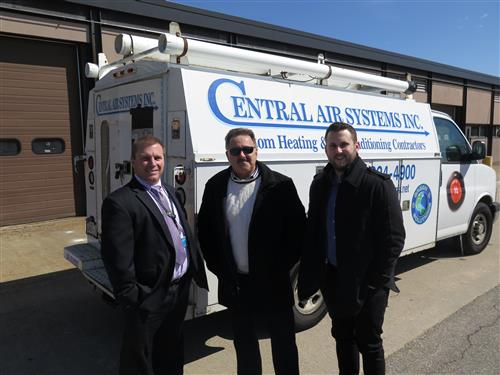 Principal McGrath, Steve Signorile and Greg Signorile pose in front of the company van.