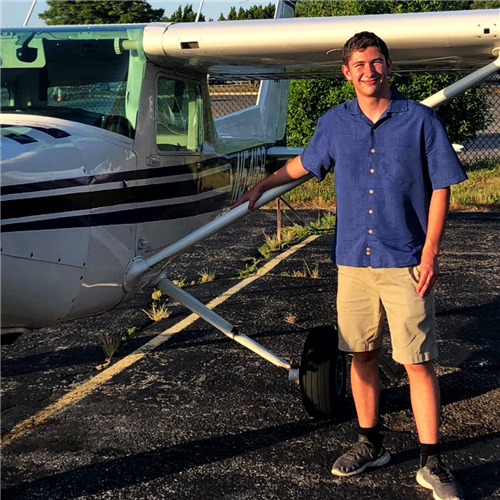 A student in a blue shirt and tan shorts stands beside a small private plane.