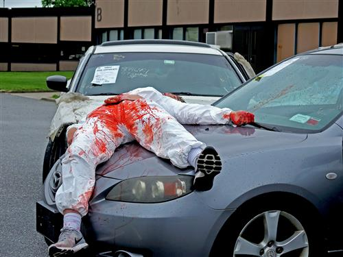 a student covered in fake blood lies on the hood of a car