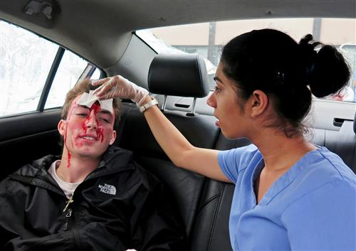 Medical Assisting students tends to the wounds of another student in this staged car accident