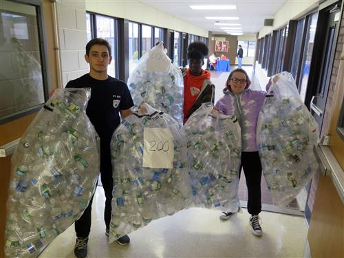 Three Law Enforcement students haul empty water bottles to the front office.