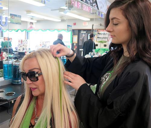 Student putting a green hair extension into the hair of Cosmetology Teacher Debbie Esposito