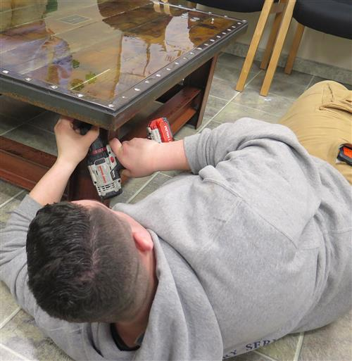 Student screwing the tabletop to the frame