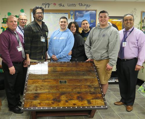 Student, teacher, adminstrators and family posing around the coffee table