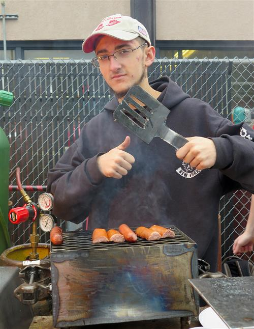 Student giving a thumbs up and holding a spatula in front of his grill