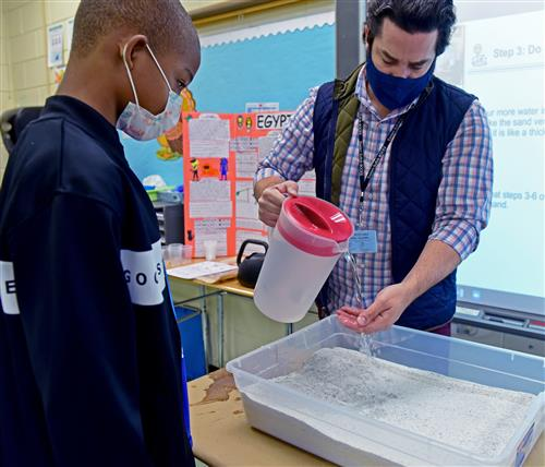 teacher pours water over sand while students watches