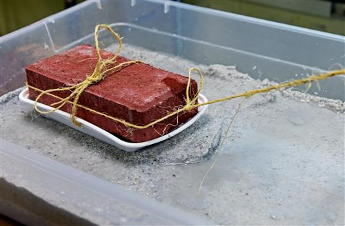 brick in tub of sand and water
